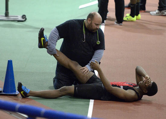 Trainer Stretches Athlete with Muscle Cramp